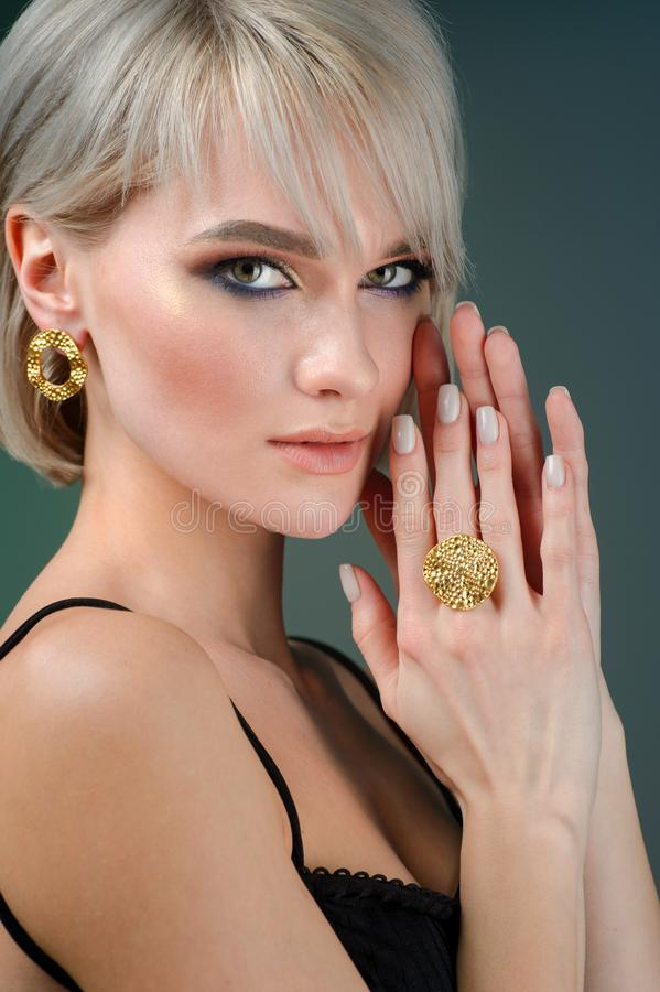 Stylish hairstyle and light makeup. Wearing earring and finger ring. on blue background. The Stylish hairstyle and light makeup. Wearing earring and finger ring stock photography