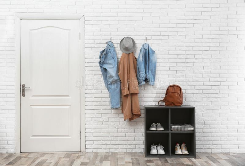 Stylish hallway interior with door, shoe rack and clothes hanging on wall stock images