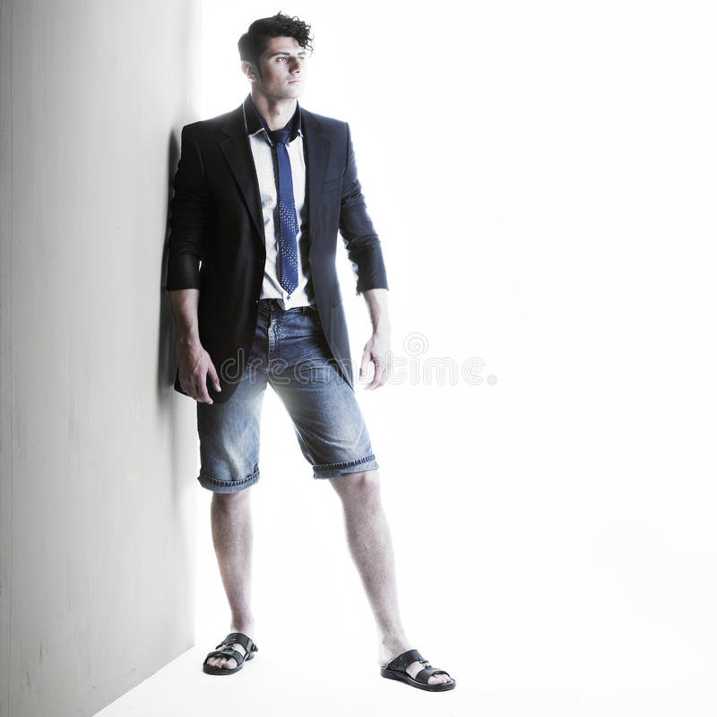 Stylish handsome men. Portrait of a handsome stylish men standing against a wall stock photo