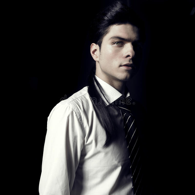 Stylish handsome men. Portrait of handsome stylish men looking out of the darkness stock images