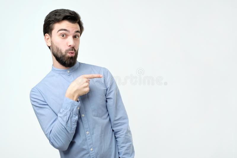 Stylish handsome young hispanic man pointing aside. royalty free stock photography