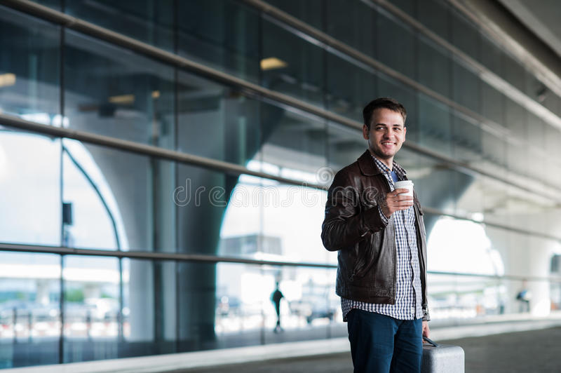 Stylish handsome young male traveller with bristle standing outdoors. Man wearing jacket and shirt. Smiling person royalty free stock image