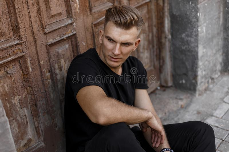 Stylish handsome young man in black t-shirt stock images