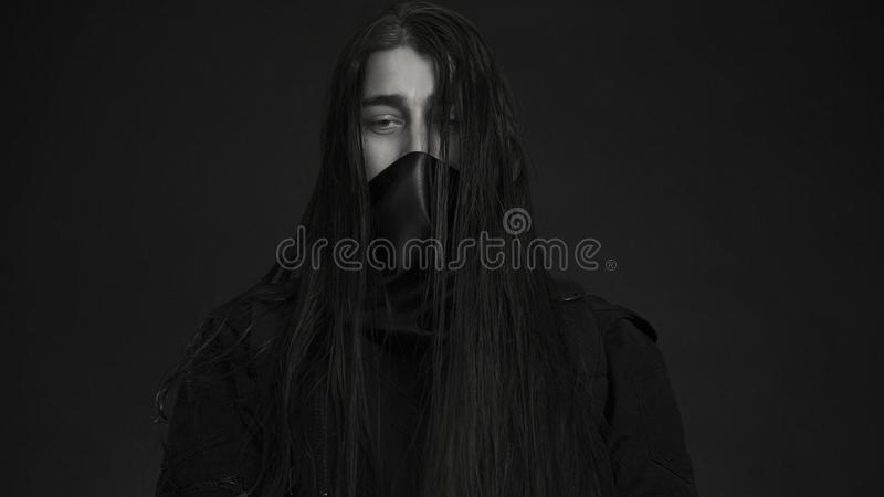 Stylish handsome Young man. Caucasian man`s portrait. man in black clothes with dark long hair royalty free stock images