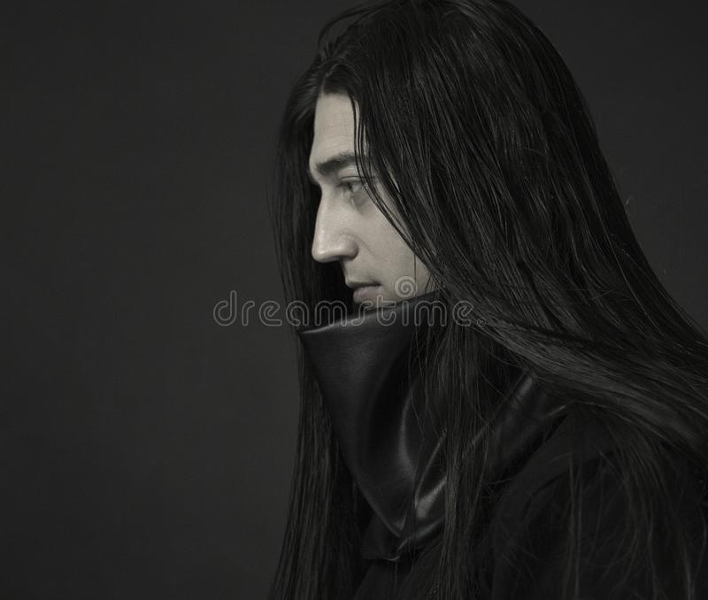 Stylish handsome Young man. Caucasian man`s portrait. man in black clothes with dark long hair royalty free stock photos