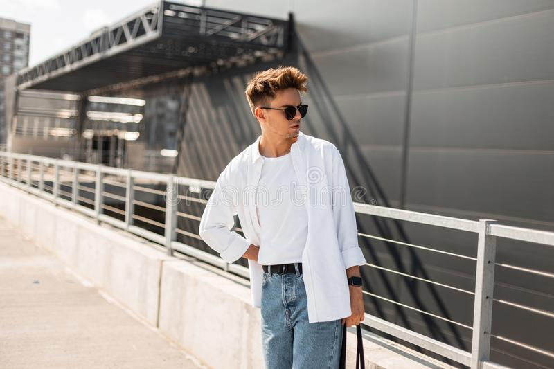 Stylish handsome young man hipster in sunglasses in fashionable clothes with trendy hairstyle with bag posing. Near a modern building on a sunny day outdoors royalty free stock image