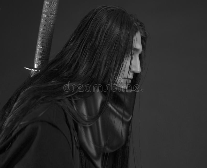 Stylish handsome Young man with Japanese katana sword. Caucasian man`s portrait. Man in black clothes with dark long hair. Close-up man`s face on a dark royalty free stock photography