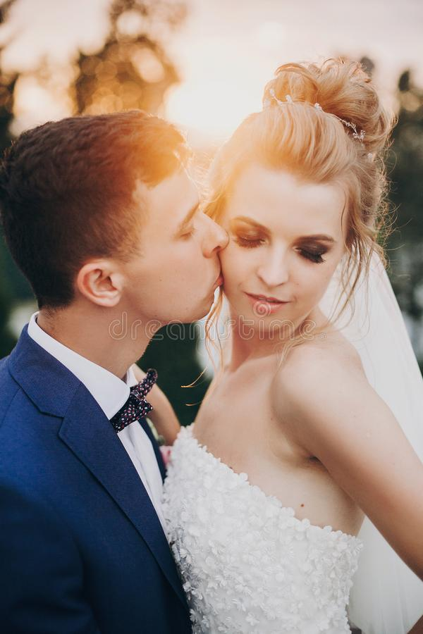 Stylish happy bride and groom kissing in warm sunset light at wedding reception outdoors. Gorgeous wedding couple of newlyweds stock images