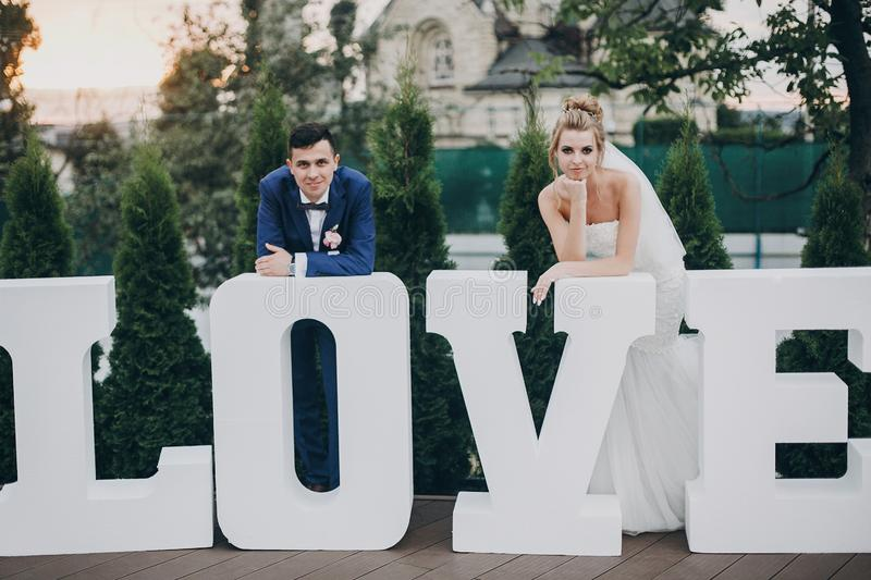 Stylish happy bride and groom posing at big love word in evening light at wedding reception outdoors. Gorgeous wedding couple of royalty free stock photos
