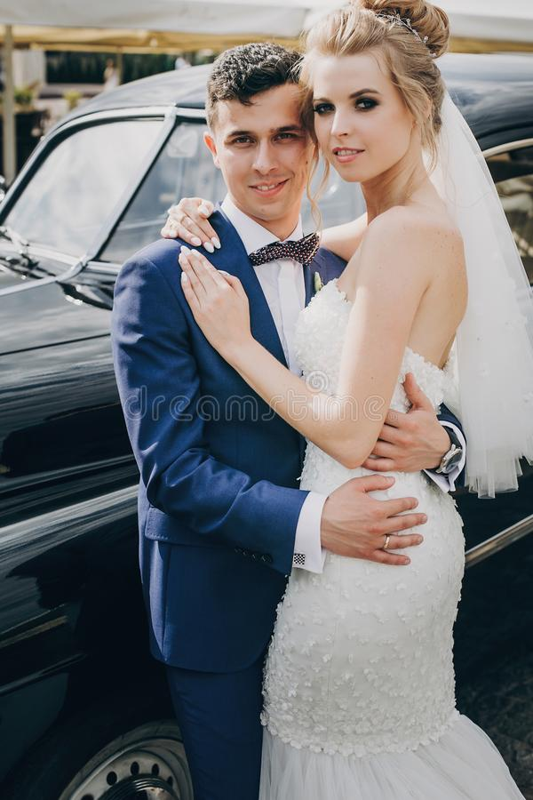 Stylish happy bride and groom posing at old retro car. Gorgeous wedding couple of newlyweds smiling and hugging after wedding stock image