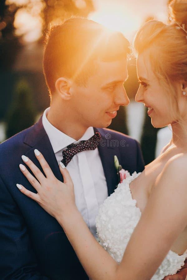 Stylish happy bride and groom posing in warm sunset light at wedding reception outdoors. Gorgeous wedding couple of newlyweds royalty free stock photo