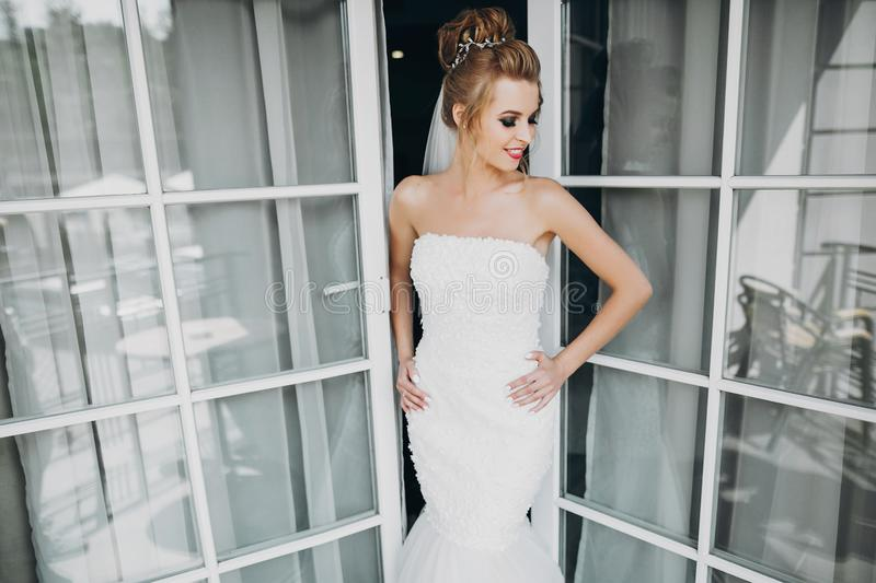 Stylish happy bride posing and smiling in soft light near window balcony in hotel room. Gorgeous sensual bride portrait. Morning royalty free stock photos