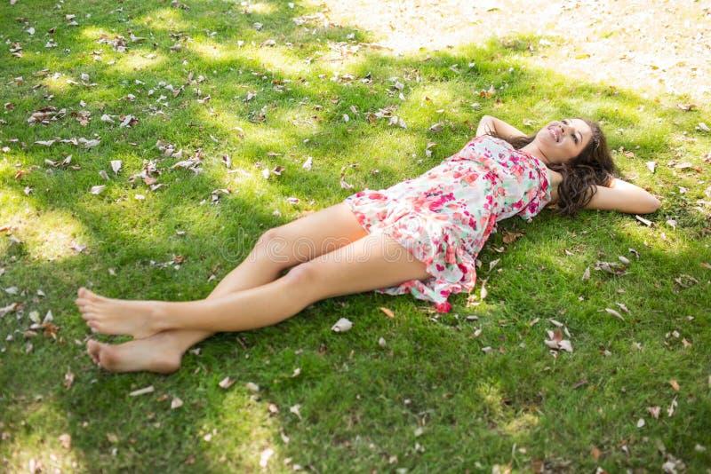 Stylish happy brunette lying on the grass royalty free stock image