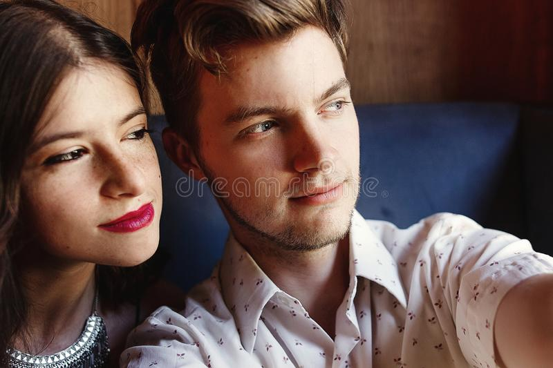 Stylish happy couple taking selfie at rich restaurant, looking a. T one direction royalty free stock photos