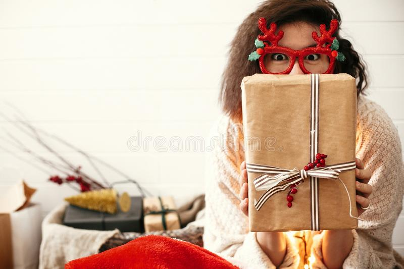 Stylish happy girl in festive glasses with reindeer antlers holding christmas gift at face in christmas lights. Young hipster. Woman in cozy sweater showing royalty free stock photos