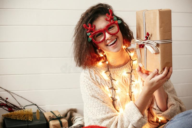 Stylish happy girl in festive glasses with reindeer antlers holding christmas gift and smiling in christmas lights. Young hipster. Woman in cozy sweater with royalty free stock photo