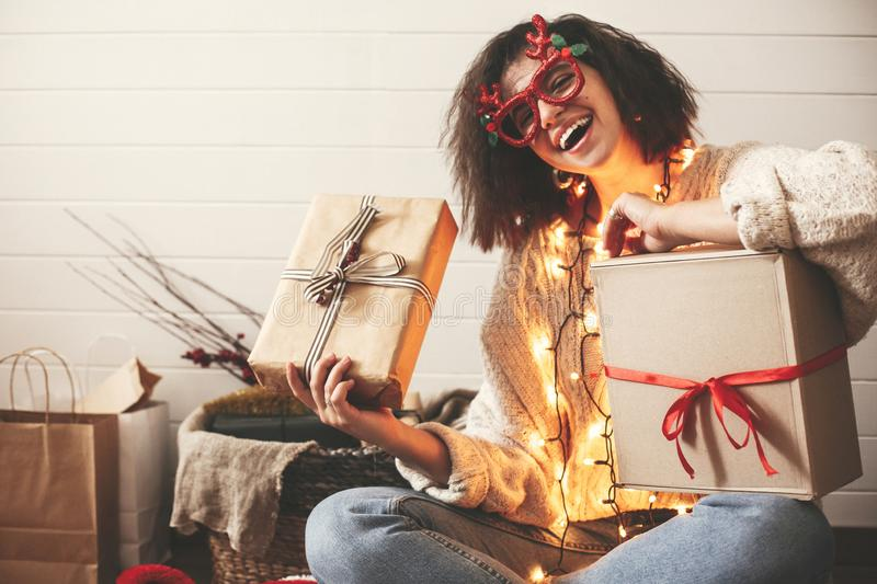 Stylish happy girl in festive glasses with reindeer antlers holding christmas gifts and smiling in christmas lights. Young hipster. Woman in cozy sweater with stock image