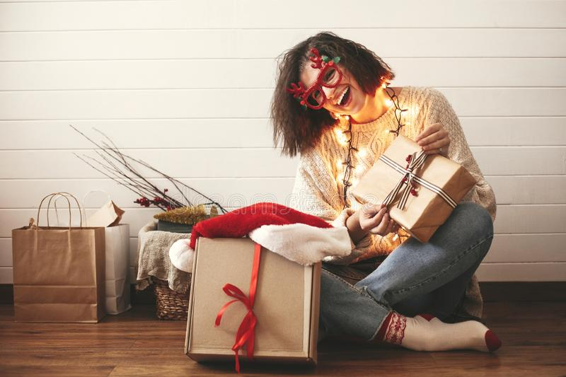 Stylish happy girl in festive glasses with reindeer antlers opening christmas gifts and smiling in christmas lights. Young hipster. Woman in cozy sweater with stock images