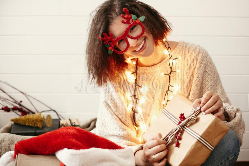 Stylish happy girl in festive glasses with reindeer antlers opening christmas gifts and smiling in christmas lights. Young hipster. Woman in cozy sweater with royalty free stock photos