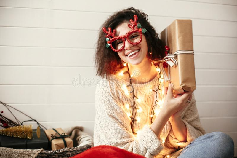 Stylish happy girl in festive glasses with reindeer antlers shaking christmas gift and smiling in christmas lights. Young hipster. Woman in cozy sweater with royalty free stock images