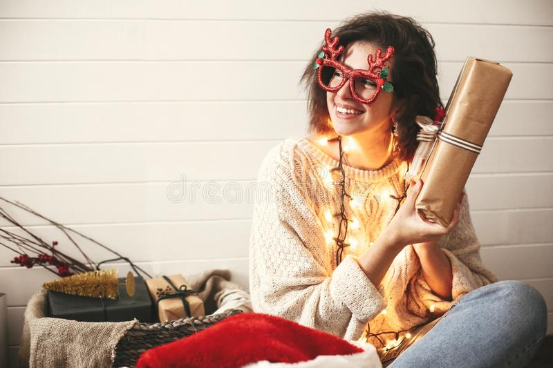 Stylish happy girl in festive glasses with reindeer antlers shaking christmas gift and smiling in christmas lights. Young hipster. Woman in cozy sweater with stock photo