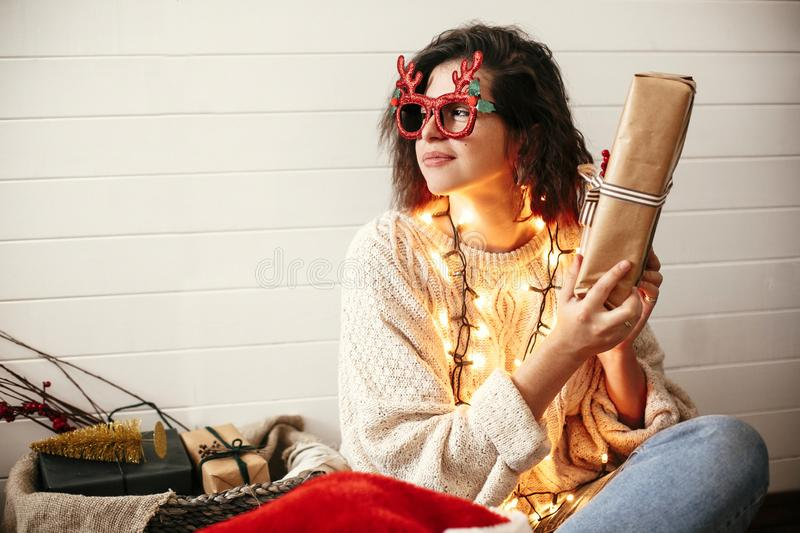 Stylish happy girl in festive glasses with reindeer antlers shaking christmas gift and smiling in christmas lights. Young hipster. Woman in cozy sweater with stock image