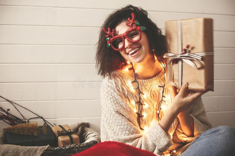 Stylish happy girl in festive glasses with reindeer antlers shaking christmas gift and smiling in christmas lights. Young hipster. Woman in cozy sweater with royalty free stock photo