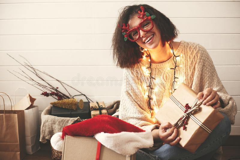 Stylish happy girl in festive glasses with reindeer antlers wrapping christmas gifts and smiling in christmas lights. Young. Hipster woman in cozy sweater with stock photography