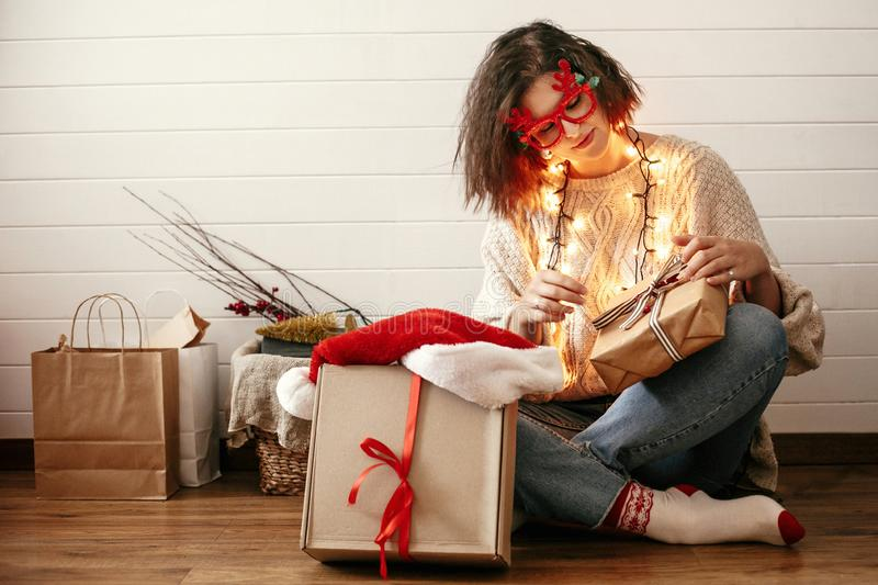 Stylish happy girl in festive glasses with reindeer antlers wrapping christmas gifts and smiling in christmas lights. Young. Hipster woman in cozy sweater with royalty free stock image