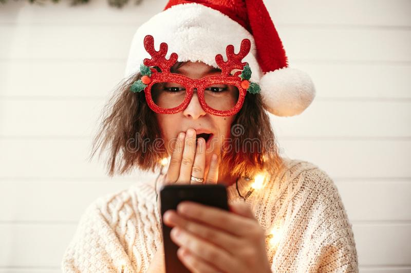 Stylish happy girl in festive glasses with reindeer horns holding phone with surprised face in christmas lights. Young hipster royalty free stock image