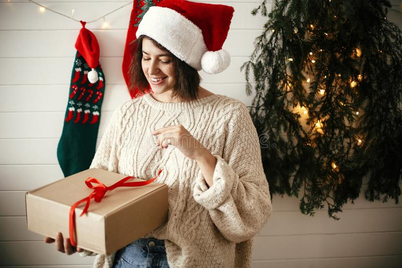 Stylish happy girl in festive sweater and santa hat opening gift box on background of modern christmas tree, lights and stockings royalty free stock photography