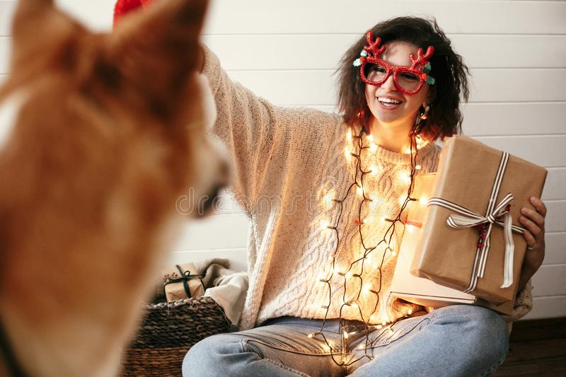 Stylish happy girl holding christmas gift box in christmas lights and smiling to cute golden dog. Young woman in festive glasses stock images