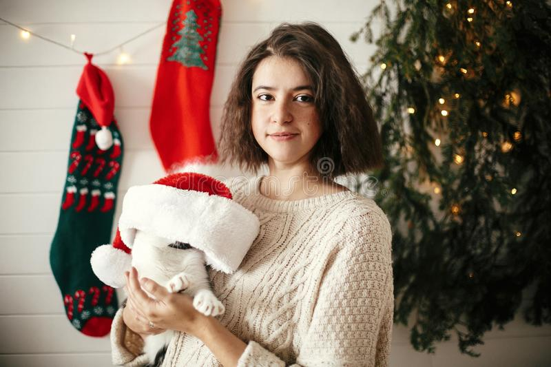 Stylish happy girl  playing with cute cat in santa hat in background of  christmas tree lights and stockings. Young hipster woman royalty free stock images