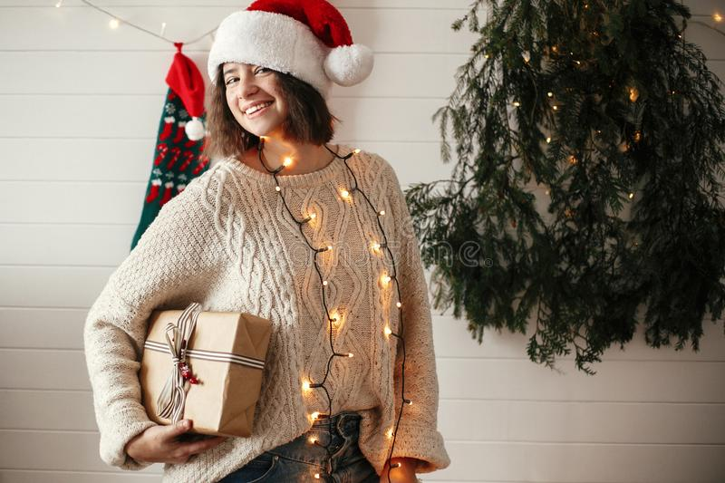 Stylish happy girl in santa hat and cozy sweater holding christmas gift box on background of modern christmas tree, lights and royalty free stock photo