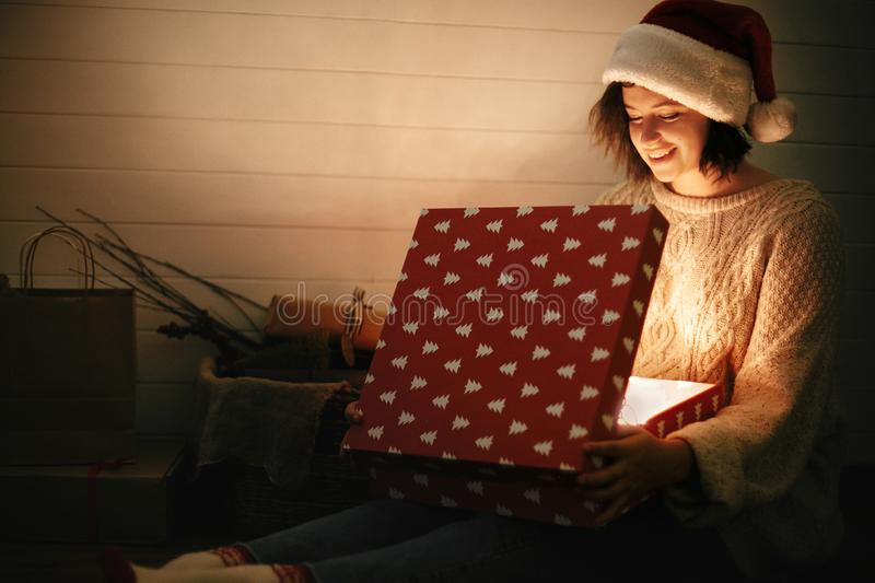 Stylish happy girl in santa hat and cozy sweater opening christmas gift box with magic light on background of presents in dark stock photography