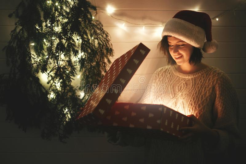 Stylish happy girl in santa hat and cozy sweater opening christmas gift box with magic light in dark room at modern christmas tree stock photo