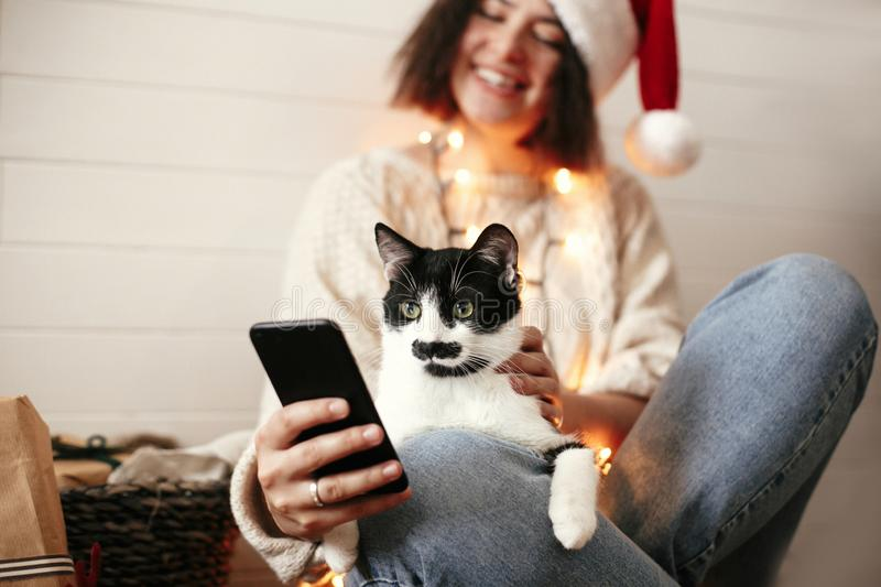 Stylish happy girl in santa hat with cute cat looking at phone screen on background of festive christmas lights and  presents. royalty free stock photography