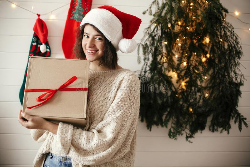 Stylish happy girl in santa hat holding christmas gift box on background of modern christmas tree, lights and stockings. Young royalty free stock photography