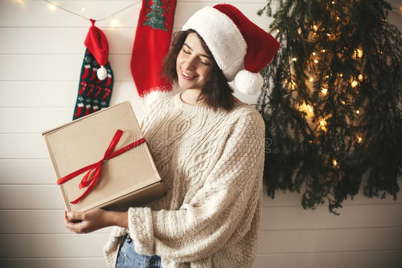 Stylish happy girl in santa hat holding christmas gift box on background of modern christmas tree, lights and stockings. Young stock photo