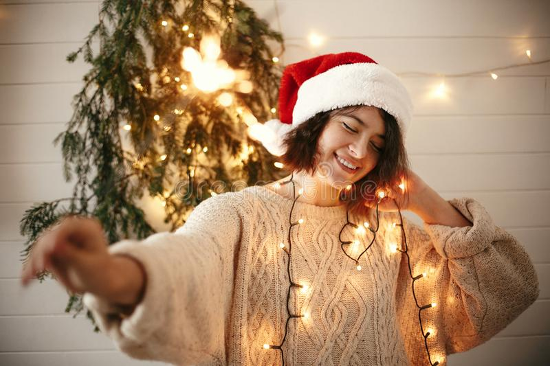 Stylish happy girl in santa hat holding sparkler on background of modern christmas tree lights in festive room. Happy New Year. Eve party. Hipster woman with royalty free stock images