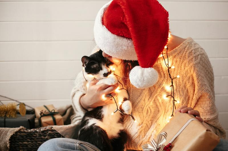 Stylish happy girl in santa hat kissing and playing with cute cat in festive christmas lights on background of modern presents. stock photography