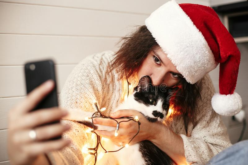 Stylish happy girl in santa hat looking at phone screen with cute cat in christmas lights on background of gifts. Young hipster. Woman in sweater hugging kitty stock images