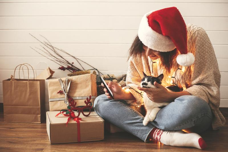 Stylish happy girl in santa hat looking at phone screen with cute cat in christmas lights on background of gifts. Young hipster royalty free stock image