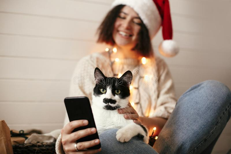 Stylish happy girl in santa hat looking at phone screen with cute cat in christmas lights on background of gifts. Young hipster. Woman in sweater hugging kitty royalty free stock images