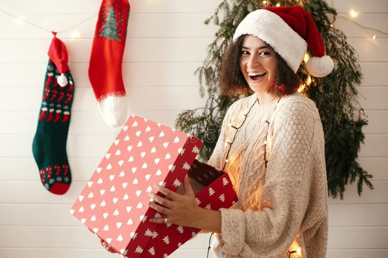 Stylish happy girl in santa hat opening gift box in christmas decorated room. Young woman in festive cozy sweater opening present royalty free stock photos