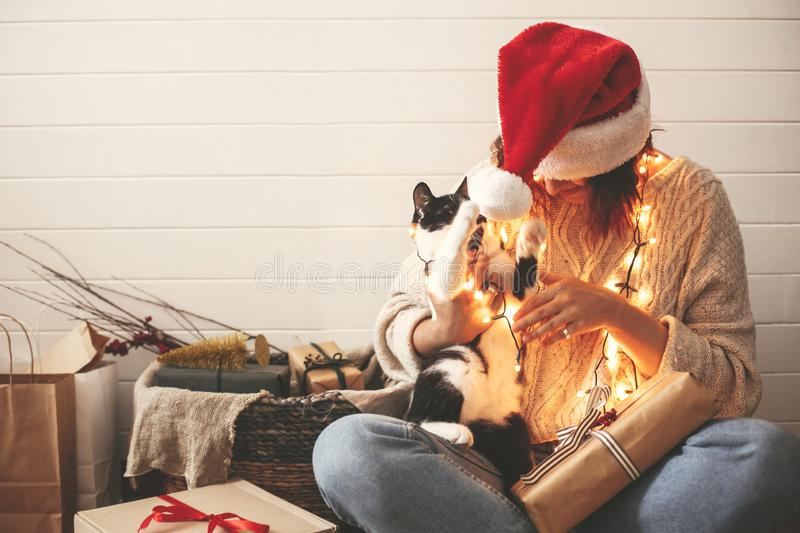 Stylish happy girl in santa hat playing with cute cat in festive christmas lights on background of modern room with presents. stock photos
