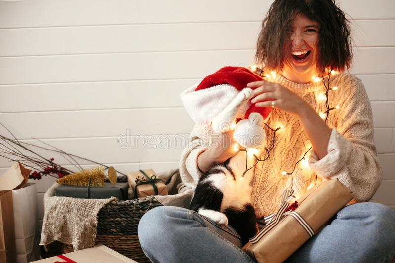 Stylish happy girl in santa hat playing with cute cat in festive christmas lights on background of modern room with presents. stock images