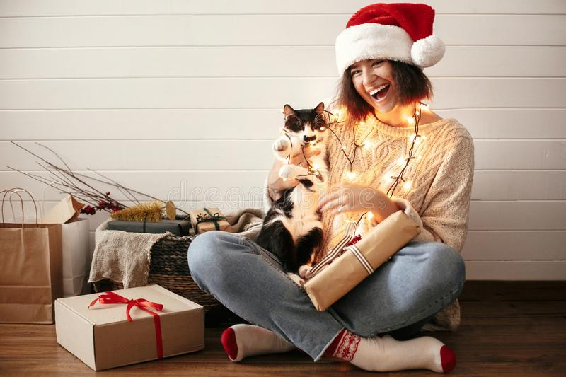 Stylish happy girl in santa hat smiling and playing with cute cat in festive christmas lights on background of modern presents. royalty free stock image