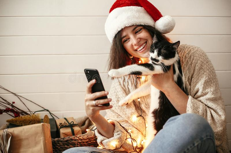 Stylish happy girl in santa hat taking selfie with cute cat in christmas lights on background of gifts. Young hipster woman in. Sweater hugging kitty with funny stock photo