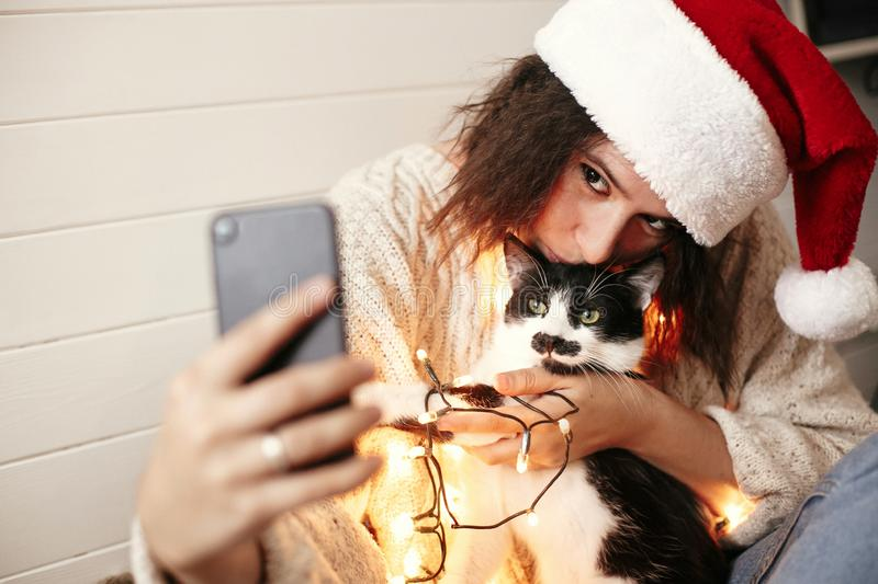 Stylish happy girl in santa hat taking selfie with cute cat in christmas lights on background of gifts. Young hipster woman in. Sweater hugging kitty with funny stock photos